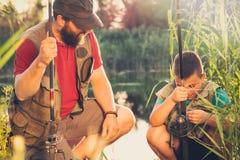 De visserspapa die in zijn zoon kijken en onderwijst hem aan opstelling een hengel stock foto