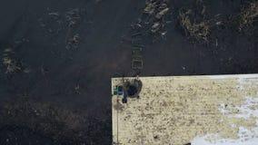 De visserszitting van de hommelmening op rivierpijler met hengel wachtende beet stock video