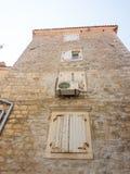 De vita träslutarna på stenväggen i gamla Budva, Montenegro Royaltyfri Bild
