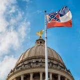 De vlag die van de staat van de Mississippi voor de capitolbouw vliegen Stock Foto