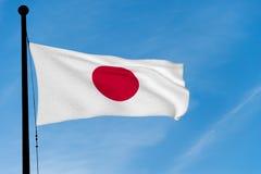 De Vlag die van Japan over blauwe hemel golven Stock Fotografie