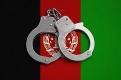 De vlag en de politiehandcuffs van Afghanistan Het concept naleving van de wet in het land en bescherming tegen misdaad stock fotografie