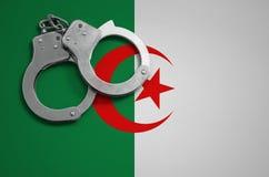 De vlag en de politiehandcuffs van Algerije Het concept misdaad en inbreuken in het land stock foto's