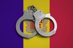 De vlag en de politiehandcuffs van Andorra Het concept naleving van de wet in het land en bescherming tegen misdaad stock foto's