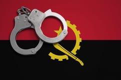 De vlag en de politiehandcuffs van Angola Het concept misdaad en inbreuken in het land stock afbeeldingen