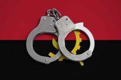 De vlag en de politiehandcuffs van Angola Het concept naleving van de wet in het land en bescherming tegen misdaad stock fotografie