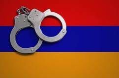 De vlag en de politiehandcuffs van Armenië Het concept misdaad en inbreuken in het land royalty-vrije stock foto