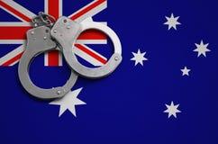 De vlag en de politiehandcuffs van Australië Het concept misdaad en inbreuken in het land royalty-vrije stock foto