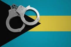 De vlag en de politiehandcuffs van de Bahamas Het concept misdaad en inbreuken in het land stock afbeeldingen