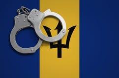 De vlag en de politiehandcuffs van Barbados Het concept misdaad en inbreuken in het land stock foto