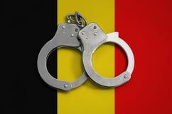 De vlag en de politiehandcuffs van België Het concept naleving van de wet in het land en bescherming tegen misdaad stock foto