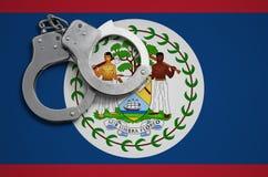 De vlag en de politiehandcuffs van Belize Het concept misdaad en inbreuken in het land stock foto