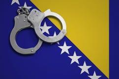 De vlag en de politiehandcuffs van Bosnië-Herzegovina Het concept misdaad en inbreuken in het land royalty-vrije stock foto's