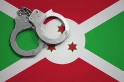 De vlag en de politiehandcuffs van Burundi Het concept misdaad en inbreuken in het land stock afbeelding
