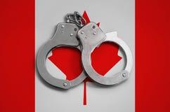De vlag en de politiehandcuffs van Canada Het concept naleving van de wet in het land en bescherming tegen misdaad stock foto's