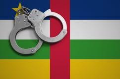De vlag en de politiehandcuffs van de Centraalafrikaanse Republiek Het concept misdaad en inbreuken in het land royalty-vrije stock foto's