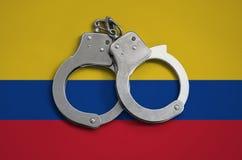 De vlag en de politiehandcuffs van Colombia Het concept naleving van de wet in het land en bescherming tegen misdaad stock afbeeldingen