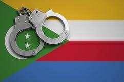 De vlag en de politiehandcuffs van de Comoren Het concept misdaad en inbreuken in het land stock afbeeldingen