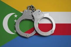 De vlag en de politiehandcuffs van de Comoren Het concept naleving van de wet in het land en bescherming tegen misdaad royalty-vrije stock foto