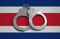 De vlag en de politiehandcuffs van Costa Rica Het concept naleving van de wet in het land en bescherming tegen misdaad royalty-vrije stock afbeelding