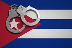 De vlag en de politiehandcuffs van Cuba Het concept misdaad en inbreuken in het land royalty-vrije stock fotografie