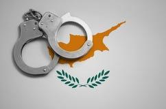 De vlag en de politiehandcuffs van Cyprus Het concept misdaad en inbreuken in het land stock afbeeldingen