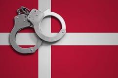 De vlag en de politiehandcuffs van Denemarken Het concept misdaad en inbreuken in het land royalty-vrije stock fotografie