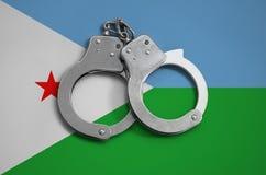 De vlag en de politiehandcuffs van Djibouti Het concept naleving van de wet in het land en bescherming tegen misdaad stock afbeelding