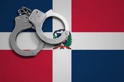 De vlag en de politiehandcuffs van de Dominicaanse Republiek Het concept misdaad en inbreuken in het land royalty-vrije stock afbeeldingen