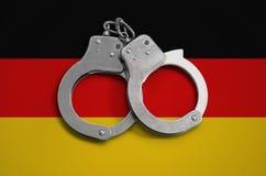 De vlag en de politiehandcuffs van Duitsland Het concept naleving van de wet in het land en bescherming tegen misdaad stock foto's