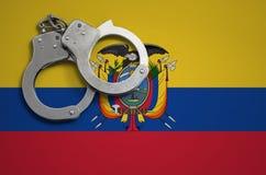 De vlag en de politiehandcuffs van Ecuador Het concept misdaad en inbreuken in het land royalty-vrije stock afbeeldingen