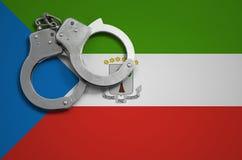De vlag en de politiehandcuffs van Equatoriaal-Guinea Het concept misdaad en inbreuken in het land royalty-vrije stock fotografie