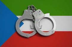 De vlag en de politiehandcuffs van Equatoriaal-Guinea Het concept naleving van de wet in het land en bescherming tegen misdaad stock foto