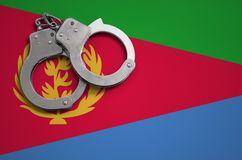 De vlag en de politiehandcuffs van Eritrea Het concept misdaad en inbreuken in het land stock foto's
