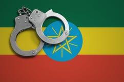 De vlag en de politiehandcuffs van Ethiopië Het concept misdaad en inbreuken in het land royalty-vrije stock afbeelding
