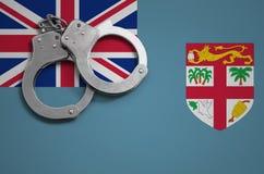 De vlag en de politiehandcuffs van Fiji Het concept misdaad en inbreuken in het land stock afbeeldingen