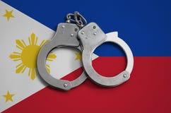 De vlag en de politiehandcuffs van Filippijnen Het concept naleving van de wet in het land en bescherming tegen misdaad stock afbeeldingen