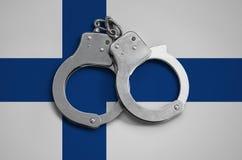 De vlag en de politiehandcuffs van Finland Het concept naleving van de wet in het land en bescherming tegen misdaad stock foto