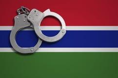 De vlag en de politiehandcuffs van Gambia Het concept misdaad en inbreuken in het land royalty-vrije stock fotografie