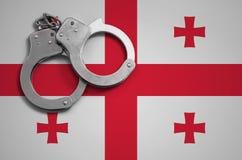 De vlag en de politiehandcuffs van Georgië Het concept misdaad en inbreuken in het land stock foto