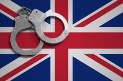 De vlag en de politiehandcuffs van Groot-Brittannië Het concept misdaad en inbreuken in het land stock fotografie