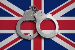 De vlag en de politiehandcuffs van Groot-Brittannië Het concept naleving van de wet in het land en bescherming tegen misdaad stock afbeeldingen