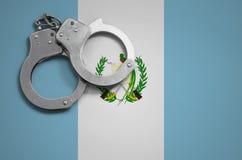 De vlag en de politiehandcuffs van Guatemala Het concept misdaad en inbreuken in het land royalty-vrije stock foto