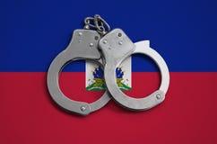 De vlag en de politiehandcuffs van Haïti Het concept naleving van de wet in het land en bescherming tegen misdaad royalty-vrije stock foto