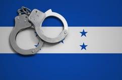 De vlag en de politiehandcuffs van Honduras Het concept misdaad en inbreuken in het land stock foto's