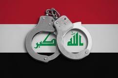 De vlag en de politiehandcuffs van Irak Het concept naleving van de wet in het land en bescherming tegen misdaad royalty-vrije stock afbeelding