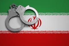 De vlag en de politiehandcuffs van Iran Het concept misdaad en inbreuken in het land stock fotografie