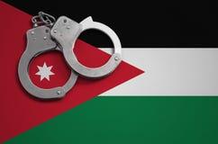 De vlag en de politiehandcuffs van Jordanië Het concept misdaad en inbreuken in het land stock foto's