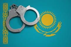 De vlag en de politiehandcuffs van Kazachstan Het concept misdaad en inbreuken in het land stock fotografie