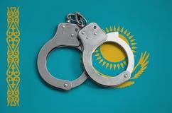 De vlag en de politiehandcuffs van Kazachstan Het concept naleving van de wet in het land en bescherming tegen misdaad stock foto's